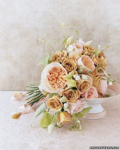 Pink, Peach, and Gold  Small tailored garden roses in buff set the stage for dramatic pink French garden roses. Clematis buds and vines tumble out between them, and generous lengths of peach silk ribbon accented with tiny gold tassels reinforce the unusual color combination.