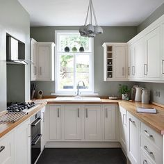 U shaped kitchen with wall units and picture window