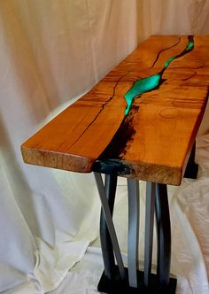 This lighted accent table is hand made from a reclaimed tigered white maple. The live edge of this tree is on the bottom/inside, with translucent turquoise epoxy to add grand character. The legs are bent wood from reclaimed hard wood, designed to resemble bent steel. Size: 52 l X 31
