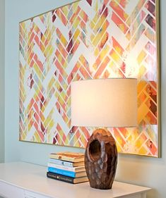 1) Paint the canvas all crazy  2) Use masking tape to create a herringbone pattern with gaps missing  3) Paint over the canvas in white  4) Remove tape and voila!