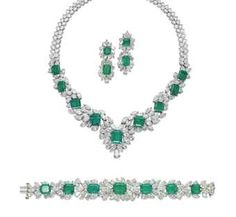 A SET OF EMERALD AND DIAMOND JEWELLERY   Comprising a V-shaped necklace set at the front with nine graduated rectangular-cut emeralds in diamond clusters, to the pear-shaped diamond backchain, a bracelet and a pair of ear pendants en suite, mounted in platinum.