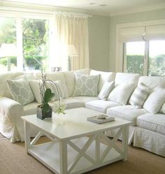 Seaside chic.  Beachy palette + slipped sofas + riad throw pillows
