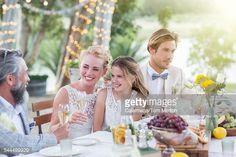 ストックフォト : Young couple and their guests sitting at table during wedding reception in garden