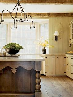 Harmonizing with its mountain-town setting, this kitchen features natural finishes and minimal fuss. The space delivers a feeling of age and hand-hewn character, despite its contemporary amenities. Fitting touches include an iron chandelier, wide-plank floors, and antiqued cabinetry. (Photo: Photo: John Coolidge; Designer: Nancy Braithwaite)