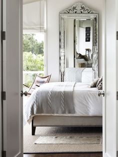 Large ornate antique silver Victorian mirror from the 1920's gives a lot of light and style to this grey & white bedroom.