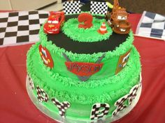 "Cars themed birthday cake-  Lightning McQueen and mater toys, fondant ""3"", checkerboard flags, fondant traffic cone, fondant ""Jaxson"" logo, fondant checkerboard ""Happy Birthday"""