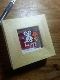 'Bee Happy' - Miniature Original Papercut This little papercut is cut from a single sheet of cream textured paper, with teeny weeny colourful floating layered flowers, and silver and black glitter detailing on the bee. Magically suspended over a red background casting pretty shadows.