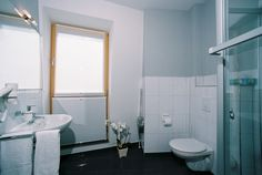 Schwarzer Granit und helle Fliesen führen die exklusive Ausstattung im Bad fort, ein Fenster im Bad sorgt für Helligkeit und frische Luft