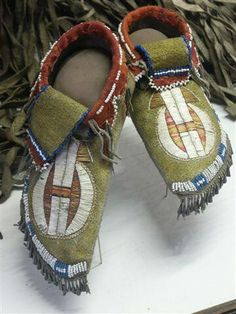 Supposedly Lakota quilled and beaded moccasins with tin cone decorations.