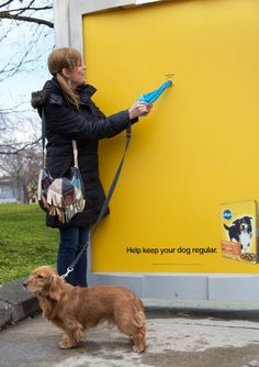 """I love this ad. If I saw this at a dog park I would definitely get a bag because my dogs always go to the bathroom when I take them for a walk. At the bottom it is adversting food and they have a sentence saying """"Help keep your dog regular."""" So they are saying that it's a good thing if your dog goes and they are rewarding people with a poop bag."""
