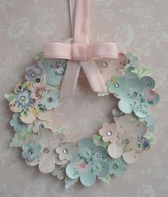 Sweet vintage wallpaper wreath! Use two different sized versions of the same punch (this shows flowers but you could do stars, hearts, leaves, etc). Punch out  a bunch of each size and layer the small ones on top of the larger, gluing them into a wreath as you go. Dot with small stick-on rhinestones for some shiny and hang with a pretty bow. Voila!