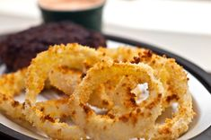 Baked Panko Onion Rings  2 large Vidalia (or other sweet) onions  1 cup all-purpose flour  1/2 tsp. salt  1/4 tsp. ground black pepper  2 eggs  1/2 cup milk  2 cups panko crumbs  Cooking spray
