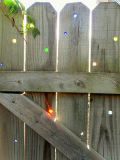 Rainbow Suncatchers ~ Glass Marbles In YourFence (Use varied size drill bits to make holes to fit randomly colored marbles/glass beads, etc). I love this! diy-outdoor-projects-ideas