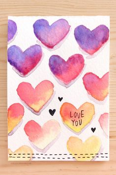"Get a little artsy with it — show off your watercolor skills with these sunset-hued ""bleeding"" hearts. Top it off with a simple message or let the hearts stand on their own. Up to you. Get the tutorial at K Werner Design »"