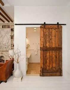 Rustic wood stain bathroom sliding doors on black iron rod to bath with clean looking decor
