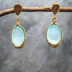 Matana handmade Chalcedony earrings These are gorgeous blue oval chalcedony earrings, pave with Swarovski crystals  and 24k gold leaf. And hanging in a 24k over silver posts. These are super stylish and UNIX. The halo is organic formed and so the earrings have a beautiful handmade overall look to it.  Convo me if you any questions. Matana Jewelry Earrings