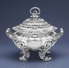 A GEORGE IV SILVER SOUP TUREEN MARK OF BENJAMIN SMITH, LONDON, 1823 Circular, on four scroll and leaf feet headed by acanthus, the fluted body with acanthus and shell rim and reeded acanthus handles, the fluted domed cover with beaded and gadrooned leaf border, surmounted by a calyx with entwined serpent finial, the body engraved with a coat-of-arms beneath a Baron's coronet, the cover engraved with a crest, with removable liner