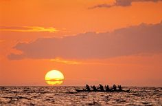 Outrigger canoe paddlers at sunset, Hawaii.