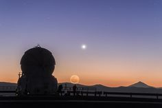 Venus and the Moon strike a pose | As the Sun raises at Cerro Paranal, in Chile, filling the sky with superb orange shades, two members of the ESO Fulldome Expedition, Babak Tafreshi (left) and Yuri Beletsky (right), are preparing their tripods and cameras for the day ahead. Above the silhouette of the Chilean mountains, the gentle smile of a crescent Moon and the bright planet Venus strike a pose for the cameras.