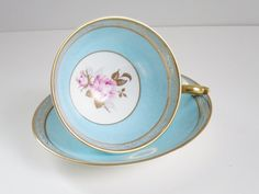 Vintage teacup and saucer by Aynsley of England in a soft aqua/sky blue mottled background, gold scroll edging and pale pink rose in the center of the cup. This piece is in perfect/mint condition showing no chips, cracks, hairlines or crazing. The mottled blue background is beautiful as it gives the cup depth, and accents the center rose. The saucer does not have a rose center.  This is a standard size teacup set and would make the perfect gift item or decor for just about any occas...
