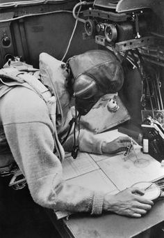 A Cecil Beaton photograph of the navigator working at his chart table in an RAF Stirling bomber, 1941., Beaton, Cecil