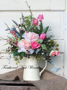 This Beautiful Spring Arrangement is made in a Creamy White Pitcher. The Pitcher WITHOUT the Arrangement Measures 9 Tall and is Around 8 Across. The Across Dimension is Measured from the Lip of the Pitcher to the Handle. I have Filled it with an Assortment of Greenery, Pink Tulips, Peach Peonies, Artificial Lavender, White Allium, Pink and Peach Roses, Bright Pink Flower Spires, Artificial Lavender, White Wispy Flowers, and Other Small Spring Florals. This is Pretty All the Way Around and…