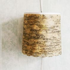 Really need to do this to the lamp in the den next to the piano. Lampshade made out of old music sheets.