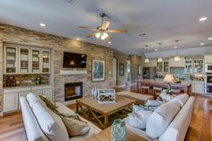 An accent stone wall emphasizes comfort and warmth through out the living room and into the kitchen. Seen in Woods of Boerne, a San Antonio community.