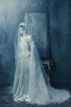 With dramatic structured shoulders and a luxurious feathered cape, this gorgeous futuristic sci-fi wedding gown would make any inter-galactic bride jealous.