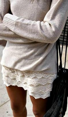 Loose-fitting sweater over embellished shorts. Light, natural colors.