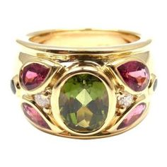 Cartier Tourmaline Sapphire Diamond Gold Band Ring. 18k Yellow Gold Diamond Tourmaline Sapphire Wide Band Ring by Cartier.  With 1 oval-shaped green tourmaline flanked by 4 pear-shaped pink tourmaline and accented by 2 round cabochon sapphires and 2 round brilliant-cut diamonds. by AislingH