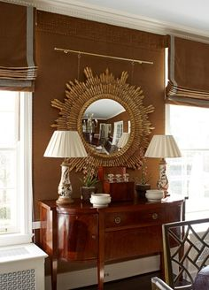 Love the color of the shades and wall and the nail head trim at the top of the wall. Beautiful sideboard and selection of accessories, and gorgeous sunburst mirror. Don't like the mirror hung from the brass rod, though.