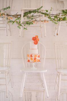 amazing way to display a wedding cake! styling by Sarah Park Events, photo by Sweet Root Village http://ruffledblog.com/orange-crush-wedding-ideas #chairs #caketable #weddingideas