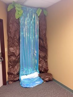 "Water was made by hanging iridescent cellophane over a blue tablecloth. ""Foam"" is a white tablecloth.  Rock columns are brown craft paper.  Greenery is tissue paper.  #waterfall  #journeyoffthemap  #Lifeway  #VBS2015"
