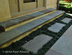 replace rocks at base of patio steps with small cement pavers - then surround with ricks or dwarf mondo grass