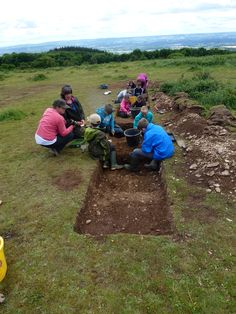 Children from Bishops Lydeard primary school taking part in a test pit excavation at Cothelstone Hill