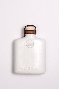 The Ceramic Flask is a drinking flask made with quarter inch ceramic white slip cast and accented with 2 leather straps, brass stud and brass button. Made in America. Specs The flask is 4.25 x 6.5 inc
