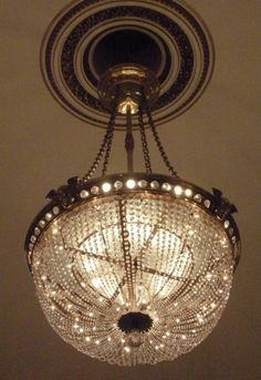 Located 2015 in the Ball Supper Room of Buckingham Palace, London, UK. Glass & Gilt Chandelier made in UK. A large hemispherical chandelier made of strings of cut-glass beads, suspended from a gilt-bronze band, pierced & studded with cut glass & with masks of Mercury & a spherical glass pendant finial.