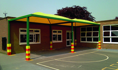 2 Yellow and green Qube canopies installed beside a school building. Colourful red and yellow leg pads for attractiveness and safety.