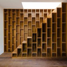 A renovated house in Tuscany with a staircase extruded from a wooden bookcase by architects Sundaymorning and Massimo Fiorido Associati.