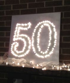 Fiftieth birthday party- traced number onto canvas. Painted silver and robin's egg blue. Drilled holes along the outline. Punched through with twinkle lights. You could even do this with an initial or monogram.