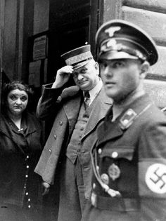 An SS officer in Vienna standing at the entrance to the Jewish community building, undated. Two faces to remember -- doorman and woman standing next to him. Black N White Images, Black And White, Warsaw Ghetto, Two Faces, German Army, Woman Standing, Sound Of Music, World War Two, Crime