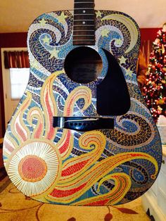 Painted acoustic guitar. I sanded the guitar, drew the design with pencil, then used acrylic paint pens and several hours to create the mosaic effect. Love the way it turned out!