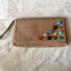 "Straw Clutch Used once. Multicolor faux stones on front. Has a platinum-colored wrist strap. Approx. 12"" x 6.5"".  Has one or two straw pieces that have split - see last photo - could be cut off and not be noticeable. New York & Company Bags Clutches & Wristlets"