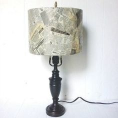 Create and artsy, vintage looking lamp shade with decoupage and old newspaper that has been weathered with age.