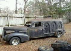 abandoned hearse, gothic arch windows.