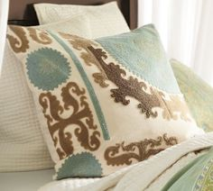 I like this pillow instead of what they picked.. bc its removable. i have dogs and a toddler, so the hundred dollar, unwashable pillows they picked are not an option: Suzani Embroidered Pillow Cover - Cool | Pottery Barn $79