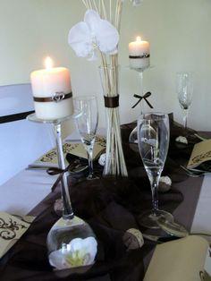 Valcové sviečky zdobené stužkou a striebornými srdiečkami na vysokých svietnikoch s orchideou