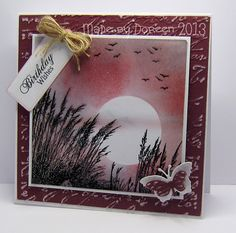 """By Doreen. Uses the """"Windswept"""" stamp from Inkylicious stamped in black VersaFine & clear embossed. Moon masked then stormy sky sponged using Distress faded jeans, rusty hinge, & barn door. Card base is white with added layer of dry embossed then sanded white-core burgundy cardstock. Stamped panel matted onto white cardstock & popped up onto card base. Sentiment, twine, butterfly added. Beautiful!"""