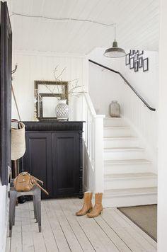 Ruime hal met witte houten trap en zwarte kast.